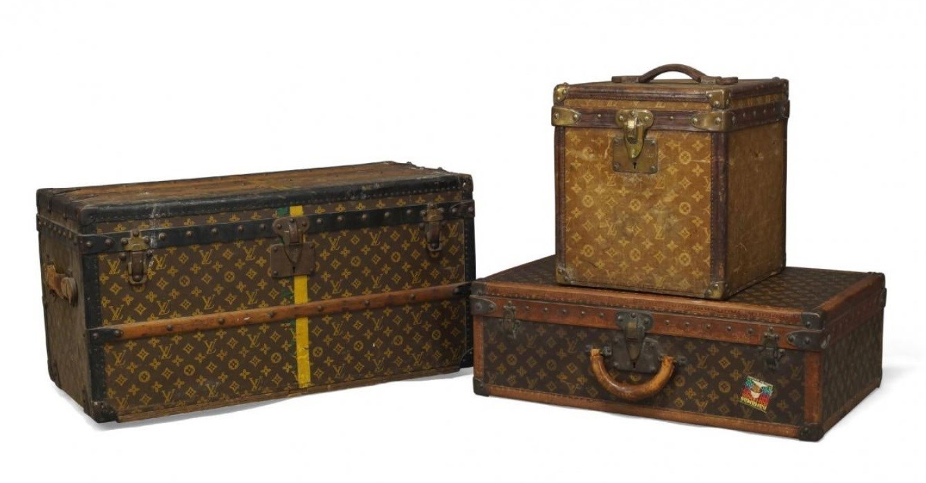 A Louis Vuitton suitcase, covered in LV monogrammed fabric