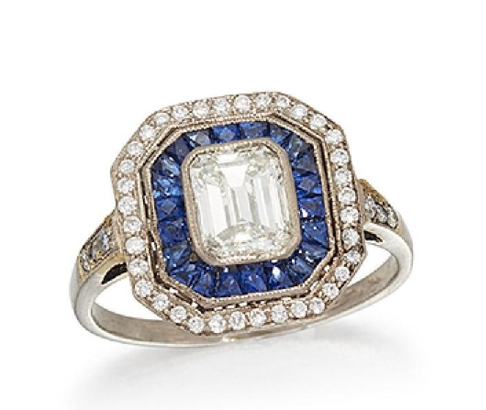 A diamond and sapphire cluster ring, the cut-cornered rectangular diamond centre to a calibre-cut sapphire border and brilliant-cut diamond surround, with brilliant-cut diamond three stone shoulders