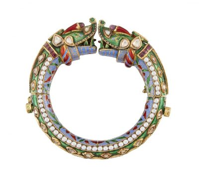 An early 20th century Indian, gold, diamond pearl, and enamel Indian bracelet (Kada), of tapering tubular form the exterior of green enamel set through out with foiled table-cut diamonds on a green enamel base