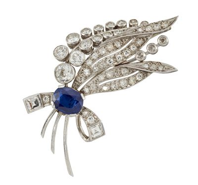 A diamond and sapphire spray brooch, designed as a collet-set old brilliant-cut diamond cluster flower with pave diamond leaves and square-cut diamond and diamond ribbon bow claw-set with a single oval-cut sapphire, circa 1950, 5.5cm long